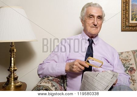 Man reading newspaper with magnifying glass
