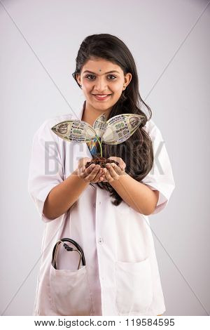 portrait of happy and surprised indian Female doctor holding a money plant or rupee plant in her bot
