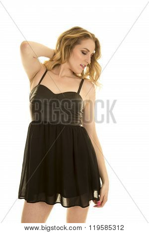 A woman in her black dress looking down to the side.