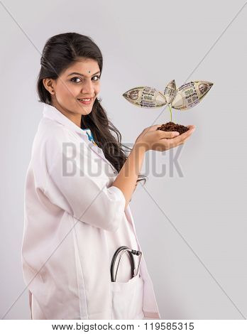 portrait of happy and surprised indian Female doctor holding a money plant or rupee plant
