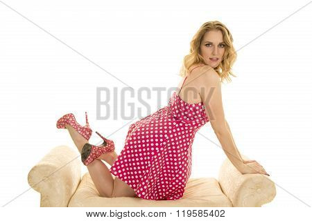 a woman kneeling down on a couch in her pink polka dot dress.