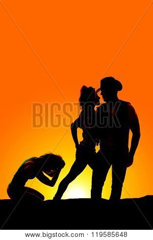 A silhouette of a woman upset while her cowboy holds another woman.