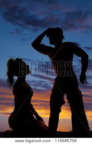 A silhouette of a woman kneeling in front of her cowboy.