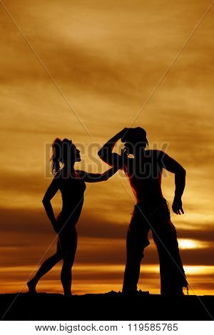A silhouette of a woman reaching out to her cowboy.