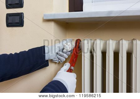 Plumber Installing A Thermostatic Valve On A Radiator