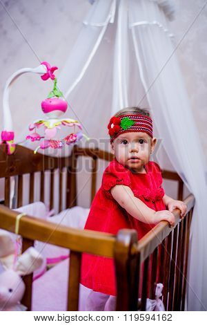 Little Girl Stands In Her Crib