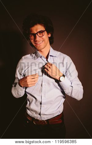 Young man businessman unbuttoning his shirt and smiling.