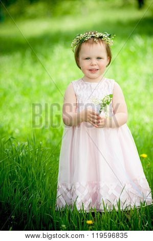 Sweet baby girl in wreath of flowers smiling outdoors
