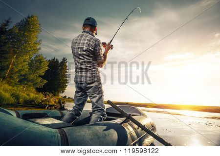 Mature man fishing on the lake from inflatable boat