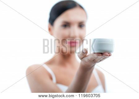 Pretty young woman is presenting great moisturizer