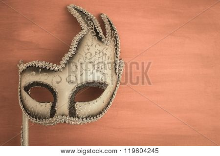 Colorful carnival mask on a brown textured background. Masks with theater concept. Top view with copy space