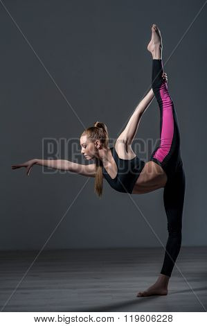Talented female athlete is doing acrobatic exercise