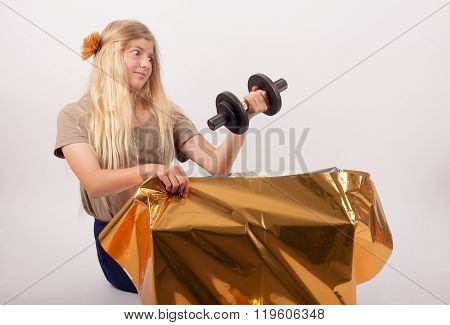 Young girl watching in amazement after unpacking her gift which is a dumbbell and suitable for men rather.