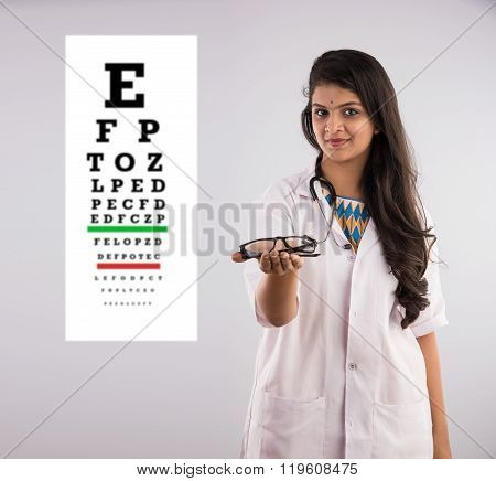 An Indian female nurse with a specs or spectacle or eye wear and eye test chart in the background, i