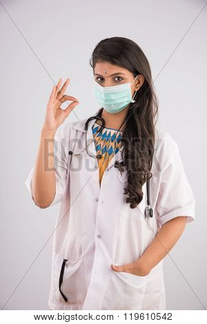 Close-up portrait of a female doctor wearing a medical mask and OK sign , asian female doctor and fa