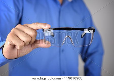 closeup clear safety glasses in man's hand