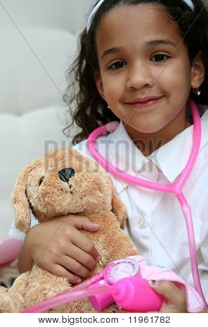 Young girl plays doctor or nurse with stuffed animal