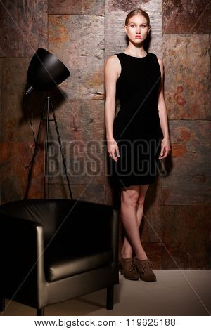 Full size studio shot of elegant blonde woman in little black dress standing over metal looking wall.