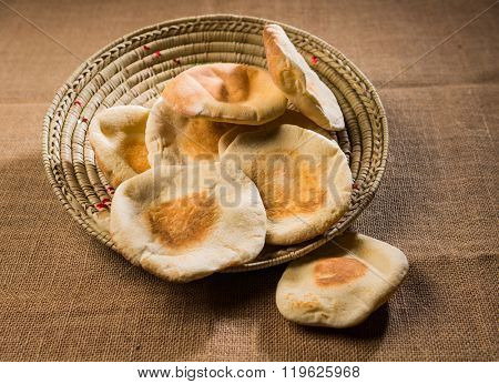 Freshly baked arabic bread. A basket full of fresh Arabic flat bread. Middle eastern food photography.