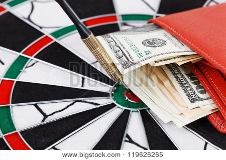 Close Up View Of Red Arrow And One Hundred Dollar Bill On Dart Board.
