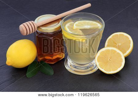 Honey and lemon drink for cold and flu remedy over slate background.