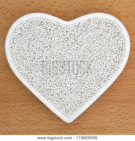 Pearl tapioca in a heart shaped dish over beech wood background.