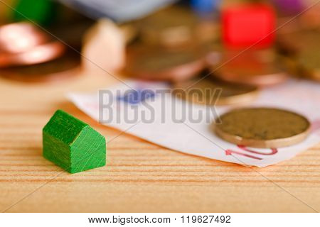 Small Green Toy House In Front Of Coins And Bills