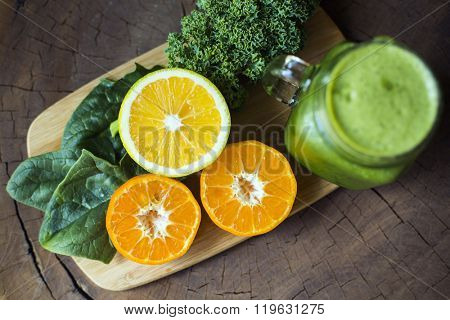 Ingredients for a green smoothie on a wooden table: spinach, kale, orange, tangerine.