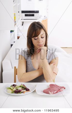 Young Woman Eating Salad And Meat