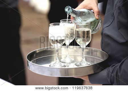 Waiter is pouring wine in the glass