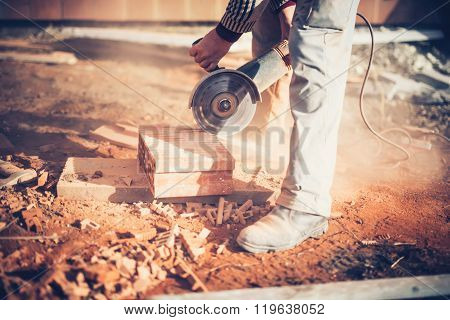 Worker Using An Angle Grinder On Construction Site For Cutting Bricks, Debris. Tools And Bricks