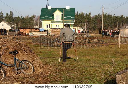 CUMAN UKRAINE - DECEMBER 02 - Man on crutches watching from afar the visit of the President of Ukraine Viktor Yushchenko in the village Cuman on December 02 2008.