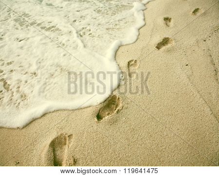 Beach holiday concept. Footprints on beach. Vintage photo