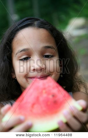 Girl eating watermelon in her yard