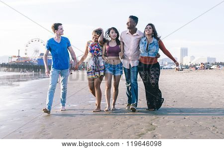 Mixed Race Group Of Friends Walking In Santa Monica Beach