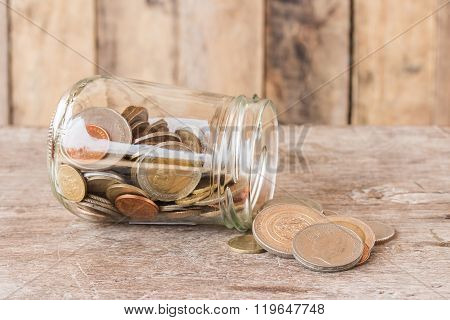 Glass Jar With Coins On Wooden Table