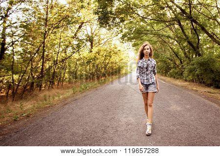 Beautiful Girl Walking On Empty Road Between Green Trees