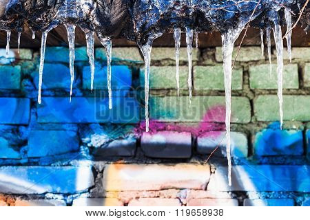 Icicles On Roof Of Shed With Painted Brick Wal