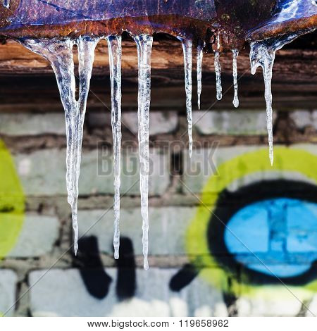 Icicles On Rusty Roof Of House With Brick Wall