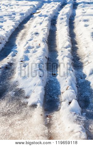 Frozen Car Tracks On Snowy Country Road
