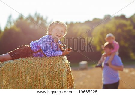 Young father and his little son having fun on yellow hay field i