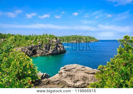natural rocky beach view and tranquil azure clear water with people in background on sunny beautiful