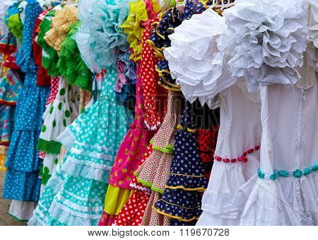 gypsy dresses hanging in a row in an andalusian Spain outdoor market