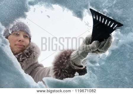 Woman Cleaning Window Of Car From The Snow With Scraper