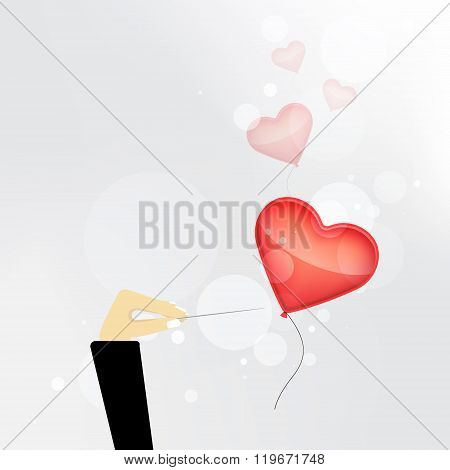 Hand with needle destroys the balloon in the form of heart