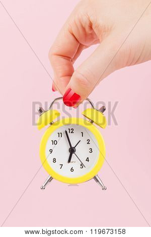 Female Hand With Yellow Alarm Clock.