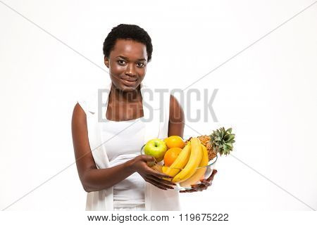 Beautiful cheerful african american young woman standing and holding glass bowl with exotic fruits over white background