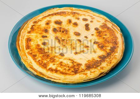 Pancakes on a blue plate white background