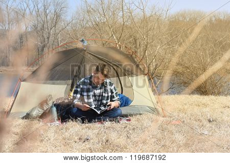 Young man reading seating outside camping tent