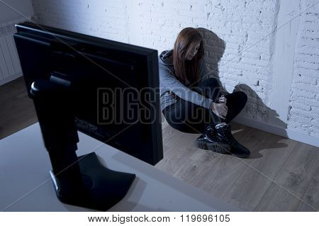 young teenager woman abused suffering internet cyberbullying scared sad and depressed in fear face expression sitting on the floor in front of computer monitor in cyber bullying social problem concept